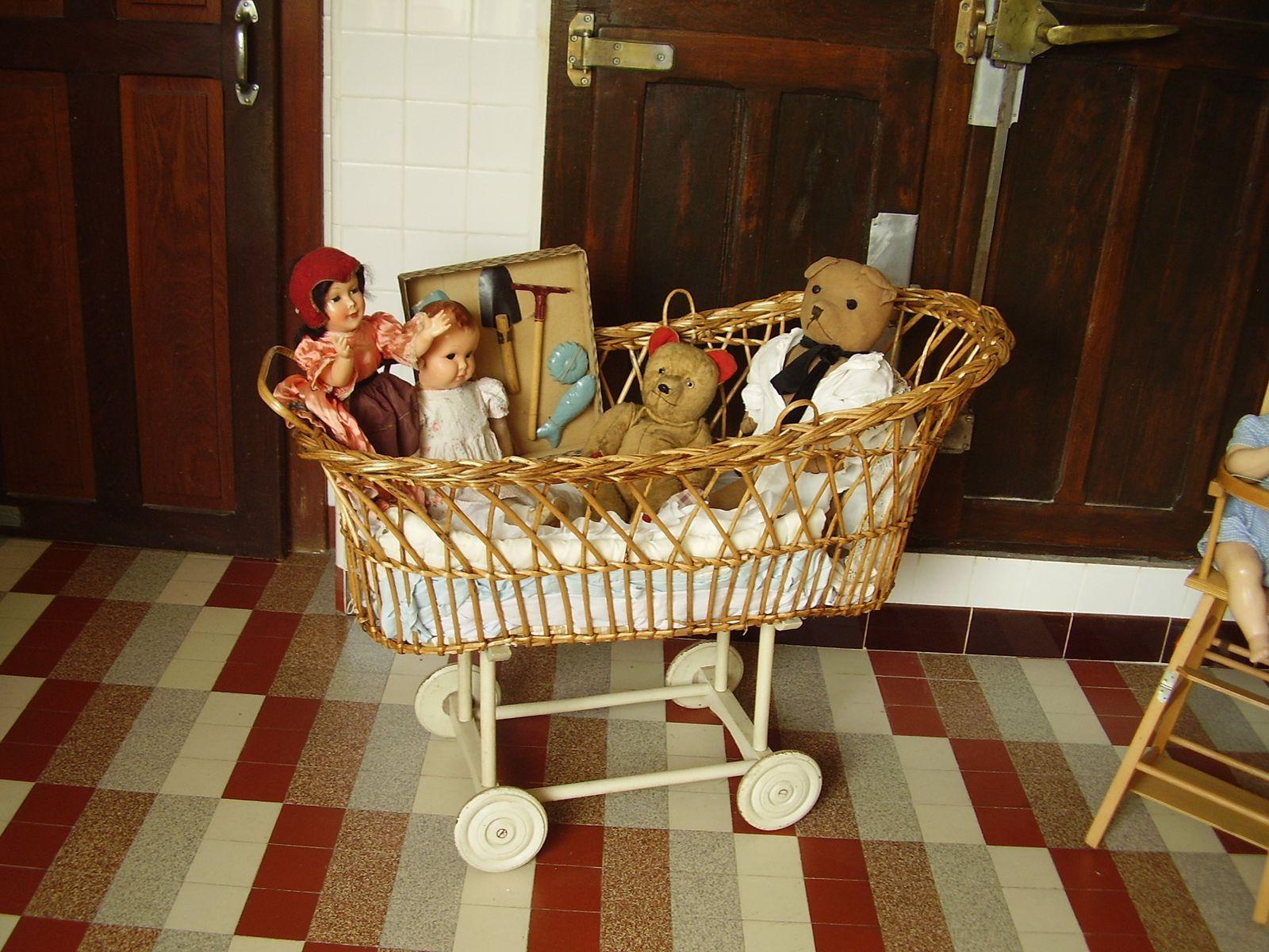 le teddy bear dans son berceau avec des poupées de 1930