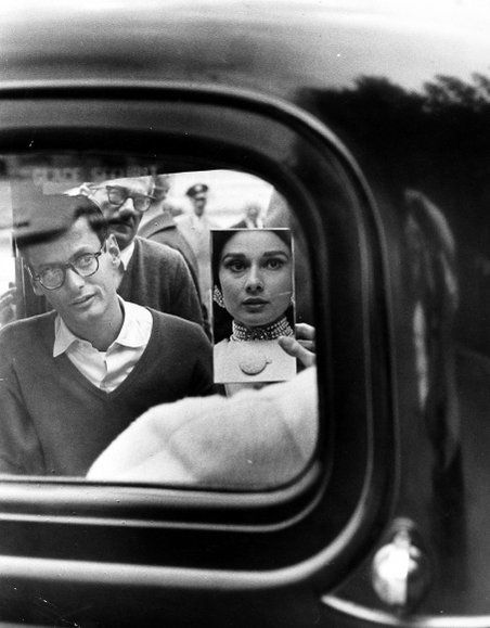 Henry Wolf : Audrey Hepburn in car, looking at herself in the mirror as Richard Avedon watches her, 1959
