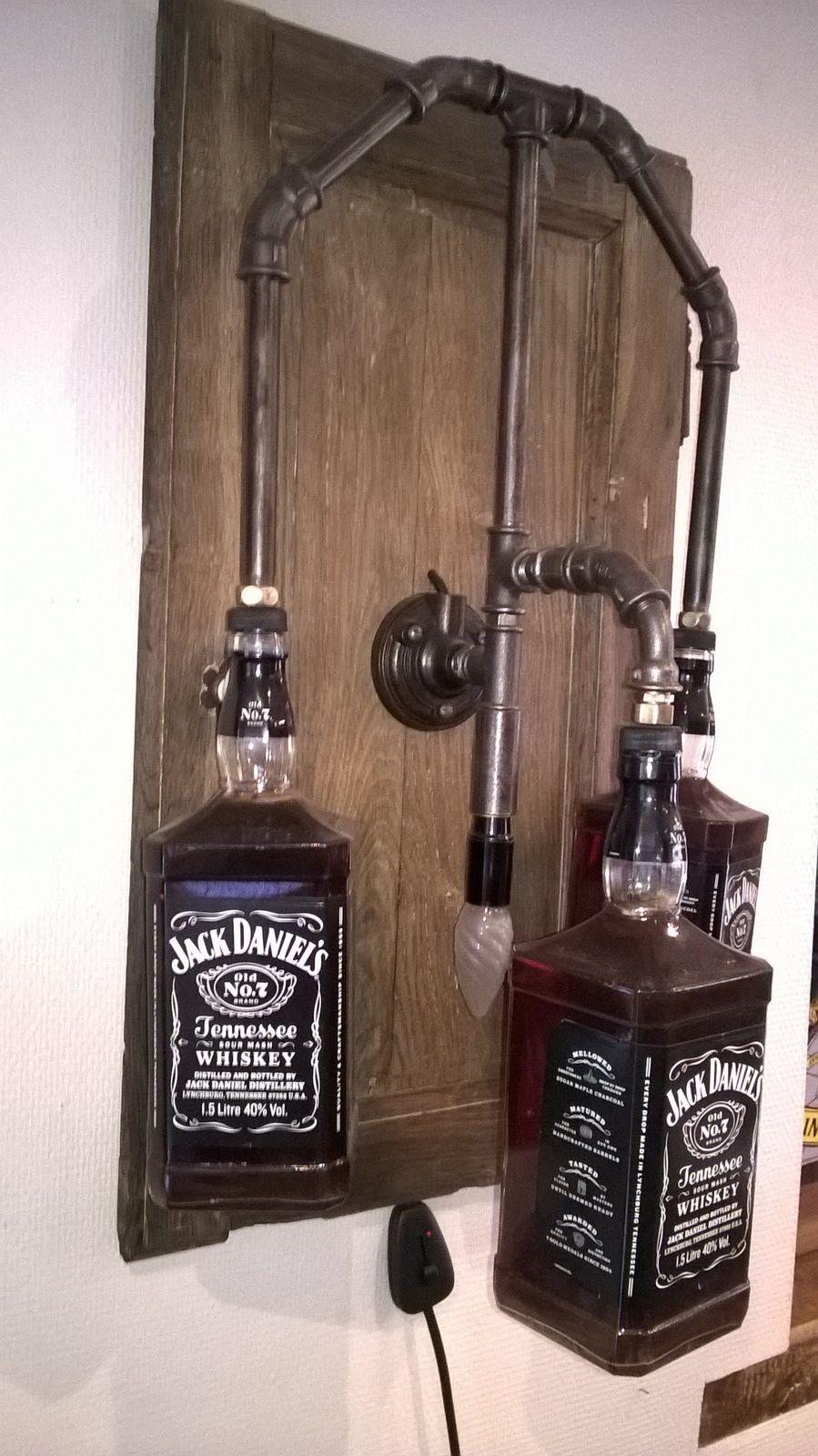 Dans la pure tradition des pendules , cette applique sur base de porte de placard en chêne . Les bouteilles de Jack Daniel's ont été bues et le contenu remplacé par du thé .