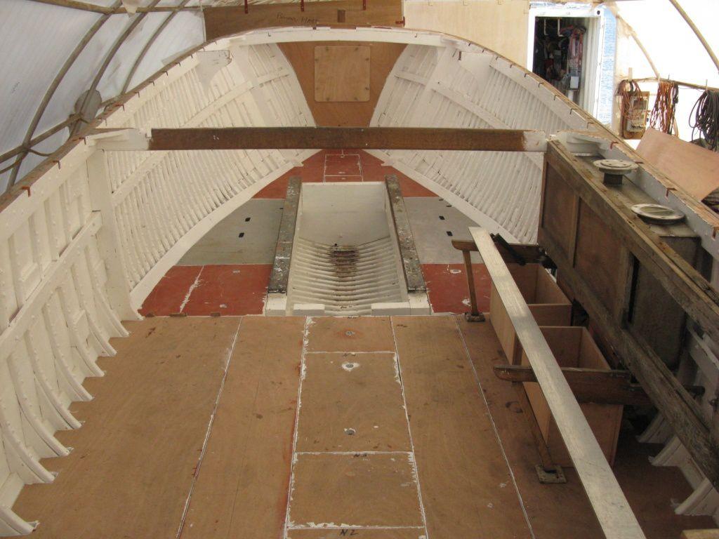 On peut voir les planchers, la cloison avant et le barrot de fixation de la cloison centrale. Sur la droite, réservoir, cloison latérale, supports du banc et bacs batteries.