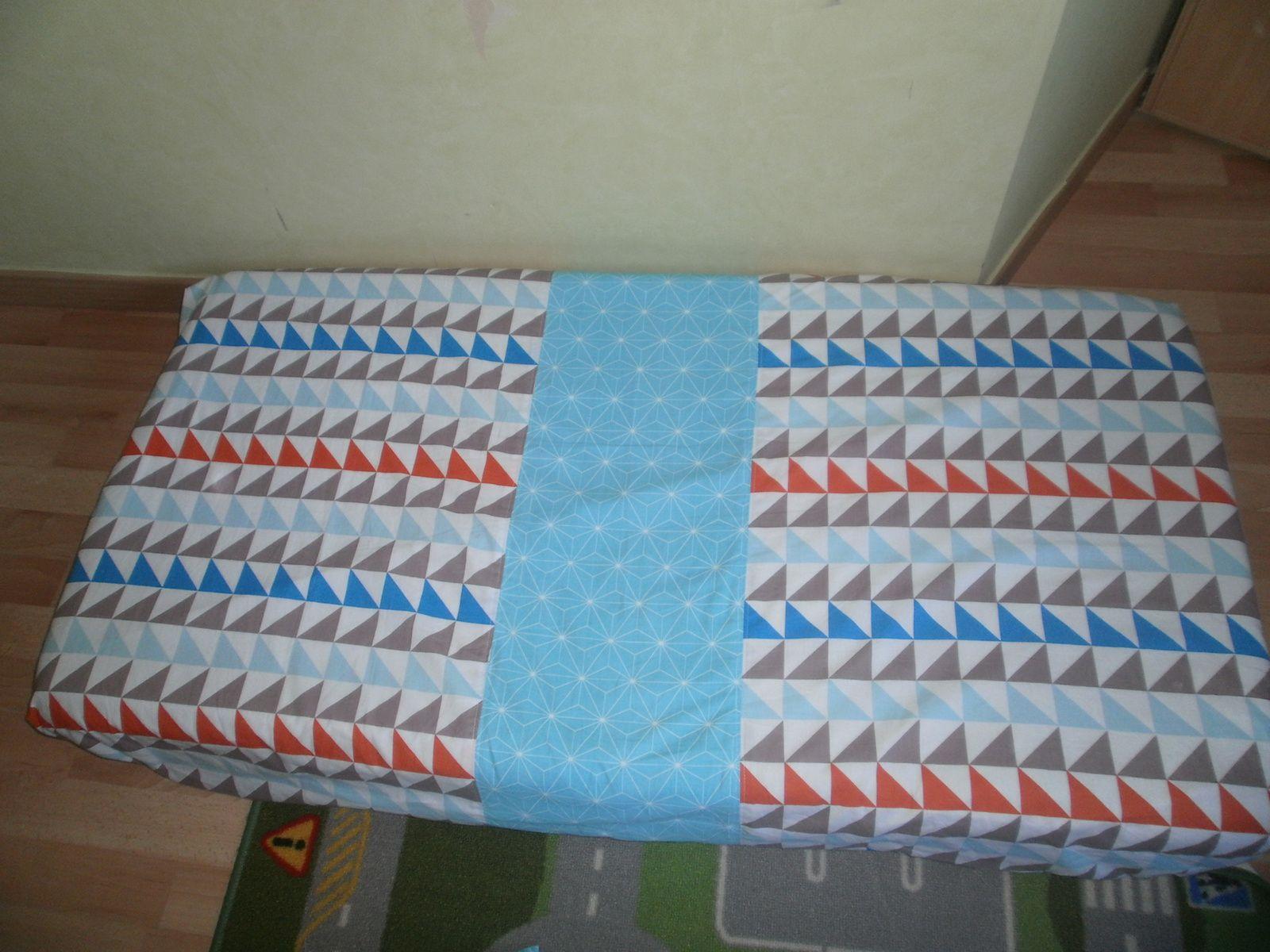 détail du matelas composé d'une bande centrale en tissu bleu clair à forme géométrique de Montial tissus et 2 bandes de tissus multicolores à formes triangulaires de Chez Mondial Tissus