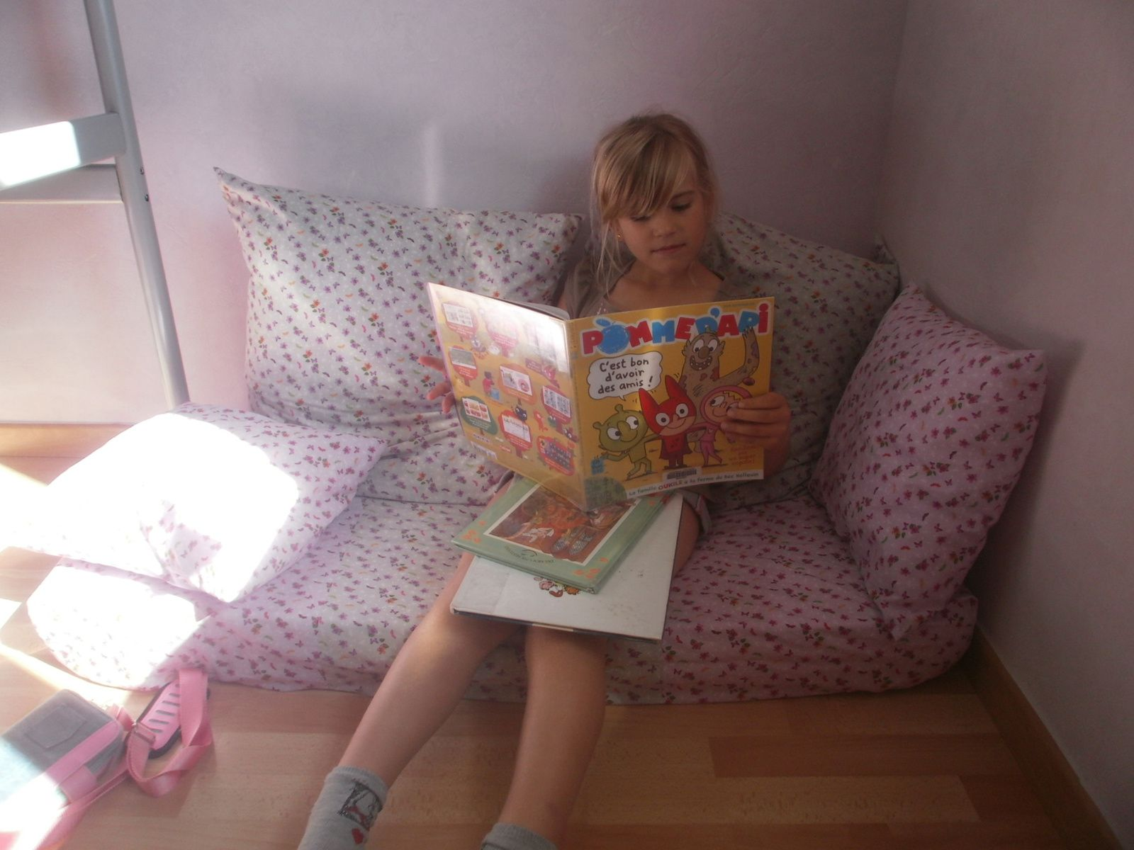 une petite fille ravie de son coin lecture