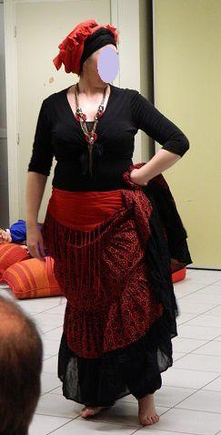 L'une des danseuses en costume tribal et danse avec voile