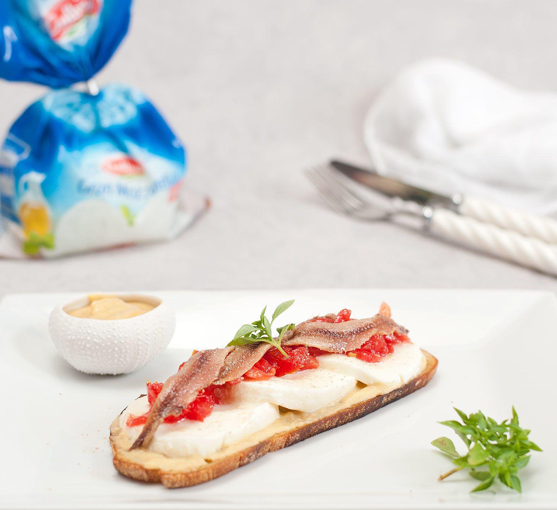 Tartine à la mozzarella, tomates concassées, houmous et anchois