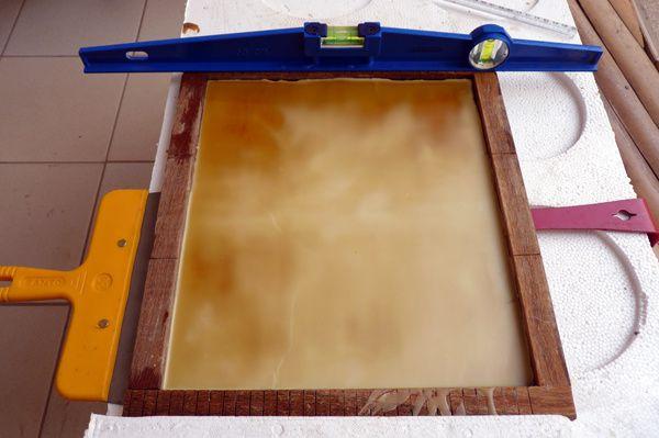 On coule la cire sur la planche. Il faut quelques minutes à peine pour que la cire se solidifie et soit prête à être découpée.