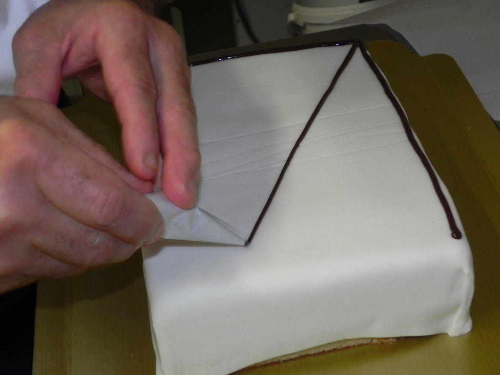 Gâteau recouvert de pâte à sucre et début de la décoration