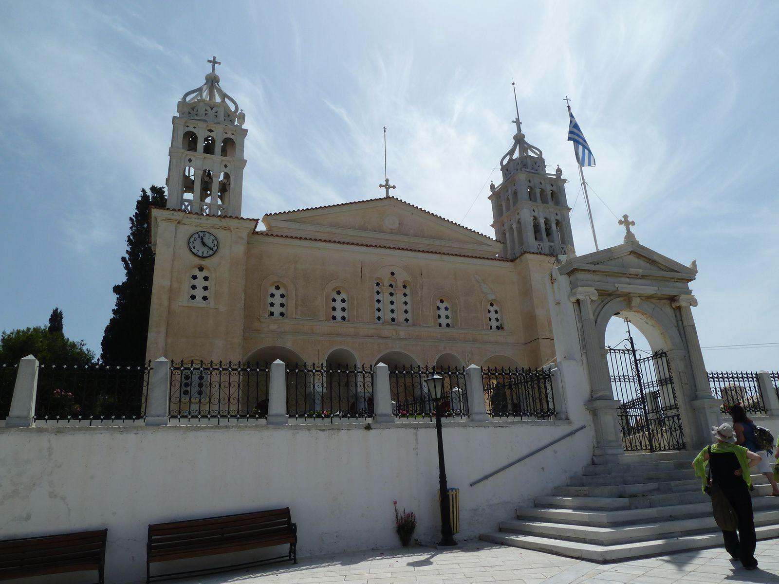 Imposant, majestueux, le sanctuaire de la Sainte Trinité de Paros (fermé) a été fondé en 1830 à l'emplacement de trois petits sanctuaires qui étaient voués à l'Ascension du Christ, à Saint Georges et à Sainte Anne, et achevé en 1835. Ce sanctuaire majestueux est une basilique à trois nefs, le toit de la nef centrale étant surélevé. Sur la façade ouest il existe une avant-nef qui est soutenue par quatre colonnes doubles de marbre de style ionique, avec des ouvertures en arcade sur trois de ses côtés, tandis que sur le quatrième, au fond, se trouvent les trois portes du sanctuaire, dont la porte centrale qui est plus élevée et plus majestueuse. Au-dessus de celle-ci a été encastrée une céramique représentant la Sainte Trinité, œuvre de l'artiste Virginia Fifa-Kydonieos. Au-dessus de l'avant-nef se trouve l'étage réservé aux femmes. A l'extérieur, le toit du sanctuaire est à deux pentes. L'intérieur du sanctuaire est lumineux. La nef centrale est surmontée d'une arcade, tandis que les nefs latérales ont des voûtes croisées. Les nefs sont délimitées par deux colonnades, chacune comportant quatre colonnes de marbre, jointes entre elles par des arches. Devant le sanctuaire se trouve une vaste cour pavée de marbre ornée d'un portail de marbre avec des colonnes et un fronton. Le sanctuaire de la Sainte Trinité de Paros a été classé monument historique protégé par le Ministère de la Culture. Tous les éléments en marbre du sanctuaire ont été fabriqués en marbre blanc de Paros. Les campaniles, véritables chefs d'œuvre, sont un exemple exceptionnel du travail des sculpteurs populaires.
