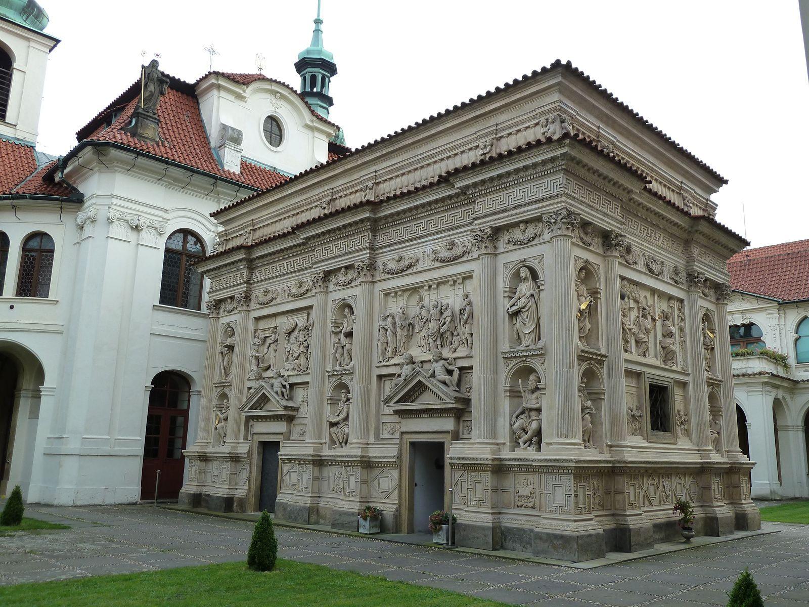Comme dans le modèle italien, la Santa Casa de Prague offre un contraste frappant entre un intérieur très modeste en brique, et une décoration extérieur luxueuse, avec des bas-reliefs en stucs représentant des scènes de la vie de la Vierge.
