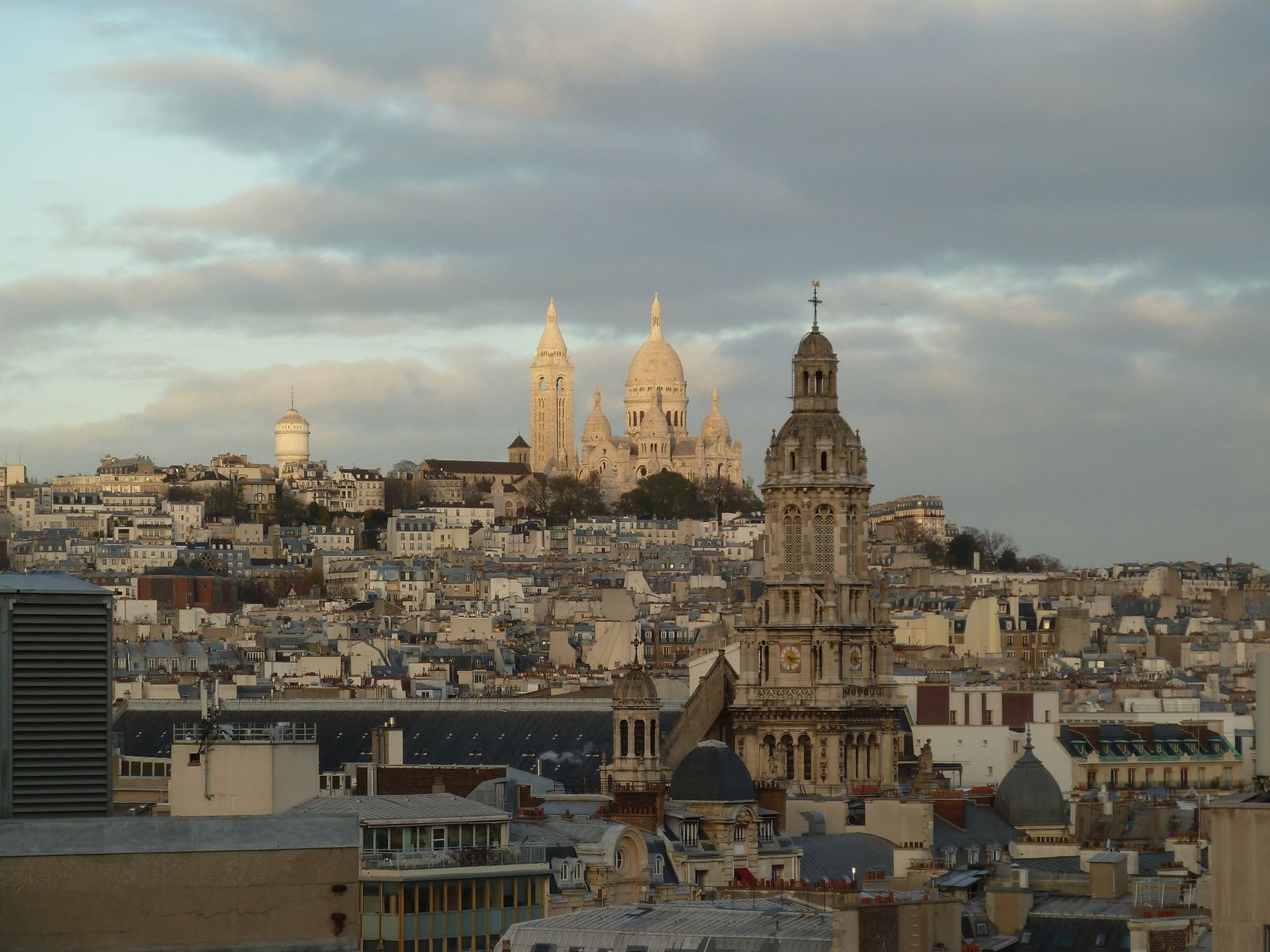Au premier plan, l'Eglise de la Trinité et la butte Montmartre avec le Sacré Chœur.