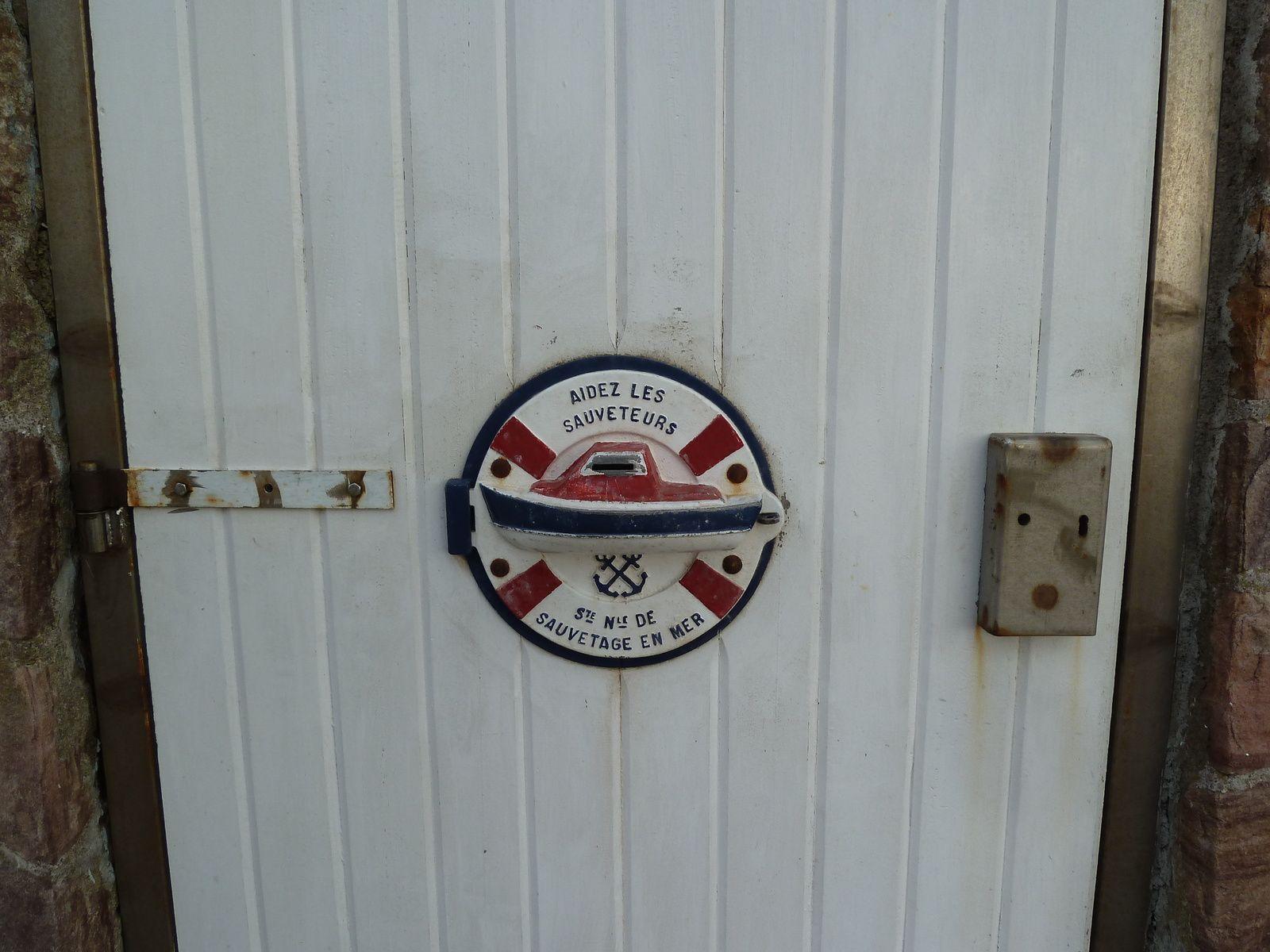 La petite tirelire où déposer son obole sur la porte du bâtiment de la SNSM (Société Nationale de Sauvetage en Mer) Fréhel-Plévenon.
