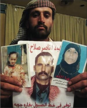 Ahmed Al-Sabooli holds the photos of his father, mother and 10-year-old sister who were killed in 2012 drone strike. (Human Rights Watch)