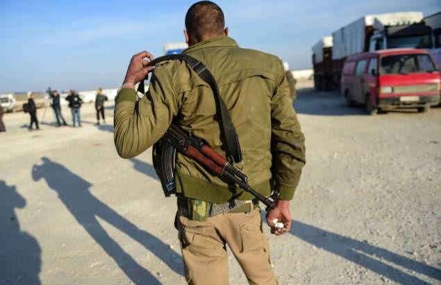 Un combattant rebelle syrien observe, le 5 février 2016 à Aazaz, des compatriotes fuyant les combats à Alep. AFP / BULENT KILIC