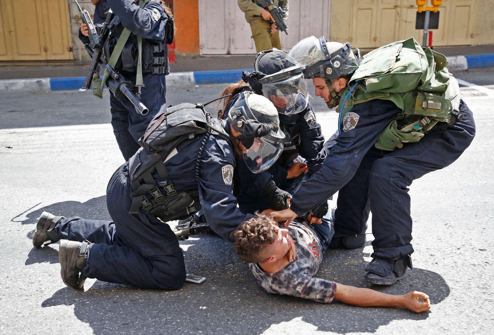 Les forces israéliennes arrêtent un jeune Palestinien lors d'affrontements entre manifestants et forces de sécurité dans la ville d'Hébron en Cisjordanie occupée par Israël, le 28 juillet 2017.Photo: Hazem Bader/AFP/Getty Images