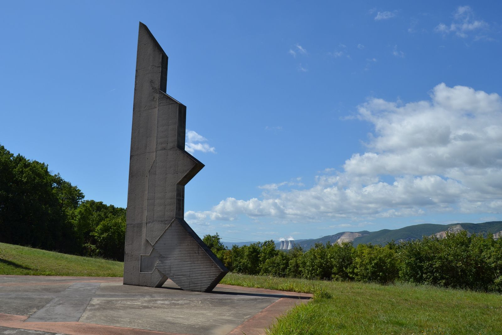 D'une hauteur de seize mètres, le monument représente, stylisé, le contour géographique du département. Il symbolise la Drôme debout. Vu sous un angle différent, il suggère, toujours stylisé, la silhouette d'un fusil‐mitrailleur.(Au second plan, les cheminées de la centrale nucléaire EDF de Cruas)