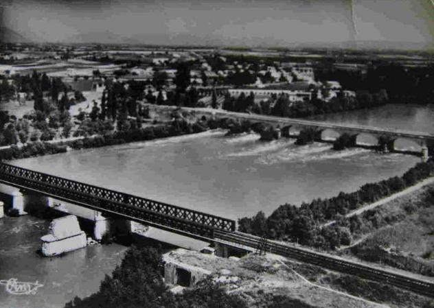 Au premier plan, la voie de chemin de fer avec, à ses côtés des piliers anciens ou passe aujourd'hui, sur une passerelles, la Via Rhôna qui reliera le lac Léman à la Méditerranée