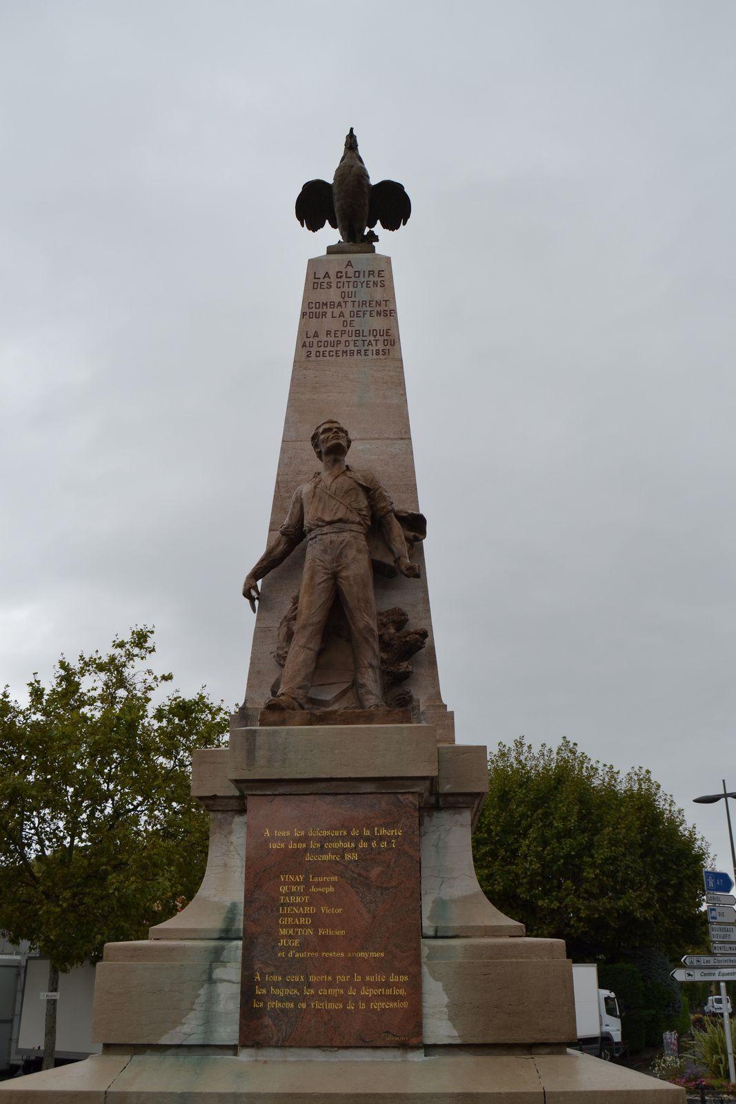 Adossé à un pylône de pierre au sommet duquel claironne fièrement un coq, la statue en bronze représente un jeune paysan, son fusil à la main, bravant du regard la tour qui lui fait face.