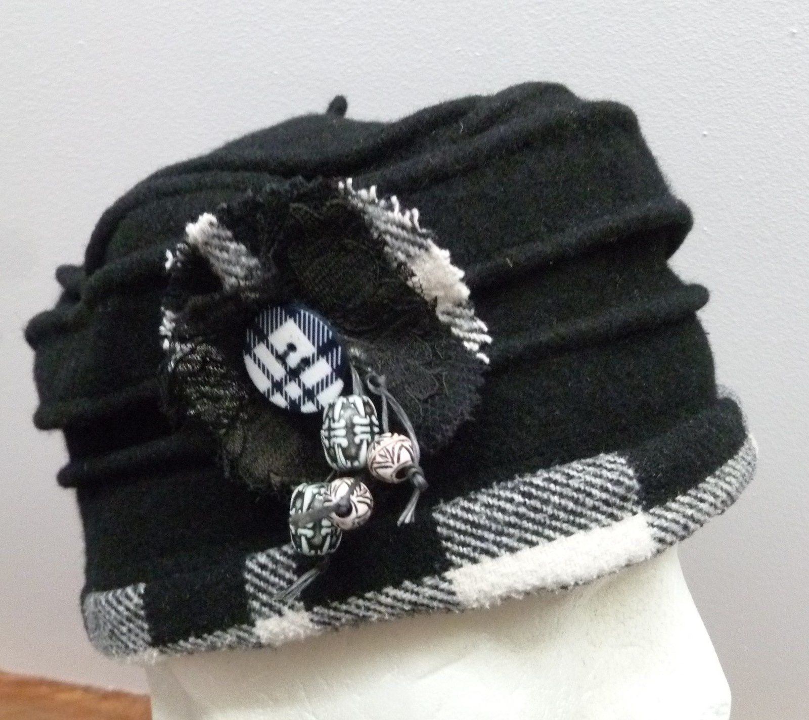 chapeau de feutre noir et lainage à carreaux .Broche et boutons coordonnées.