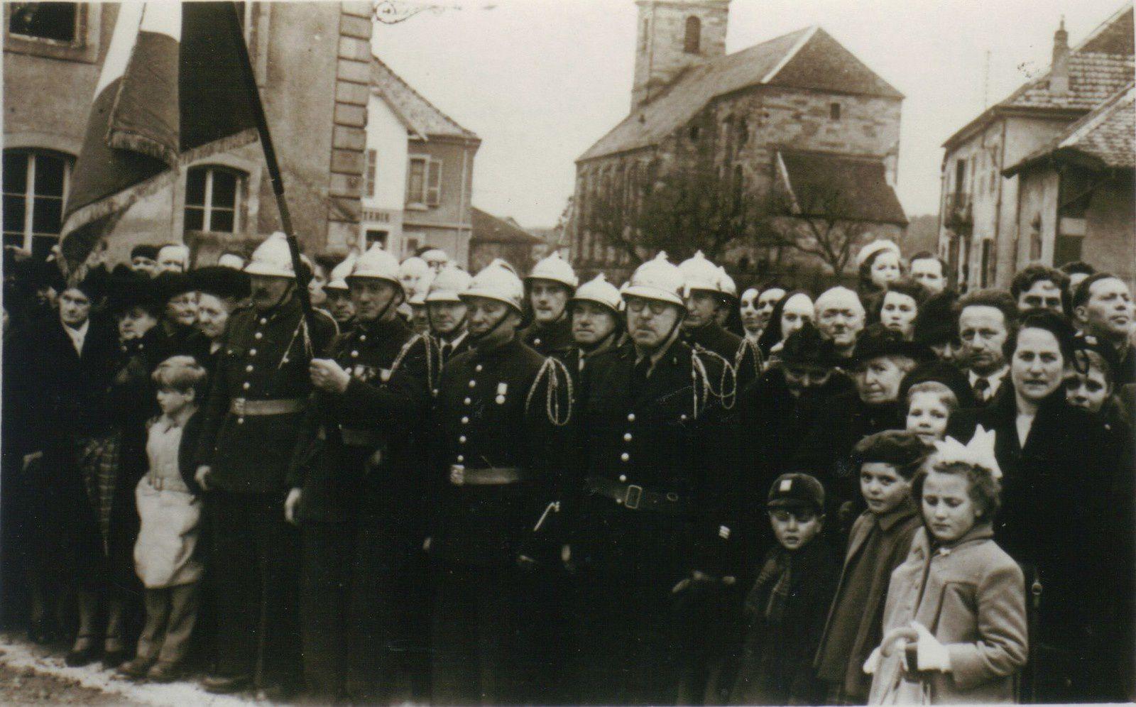 La compagnie des sapeurs-pompiers le 3 avril 1951 lors de la remise de la Légion d'honneur au curé Jeanblanc. On reconnaît au 1er rang – de gauche à droite – Henri Peroz « Tchauvey » (moustache), Edouard Jacquot (au drapeau), Eugène Couturier « Piton » et le chef Arthur Wissler (lunettes). Au 2ème rang : Henri Syriès, Gaston Didier, Mathey, Charles Wissler, Serge Méchinaud. Dans l'assistance : à gauche de Henri Peroz, Jeanne Berli, la bonne du Curé. Adroite Mme Campredon (en noir , derrière elle Lucien Millotte puis Gaston Thomassey. Au premier plan, à droite, la fillette est Nicole Grandjean (Aptel).