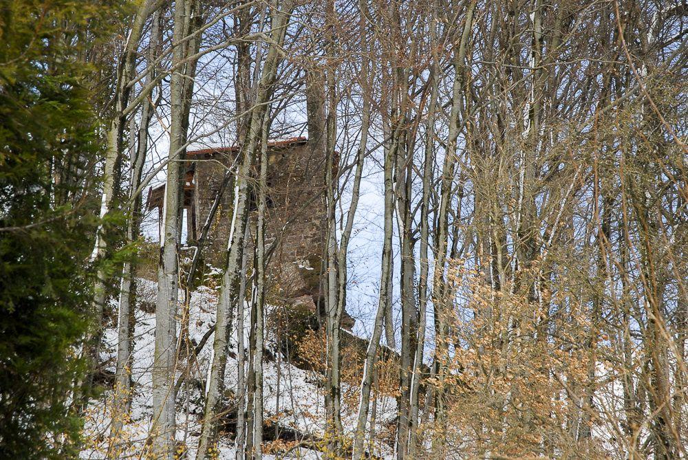 La Chapelle Saint Blaise, visible à travers les branchages d'arbres effeuillés. L'enneigement du sol fait ressortir la chapelle.