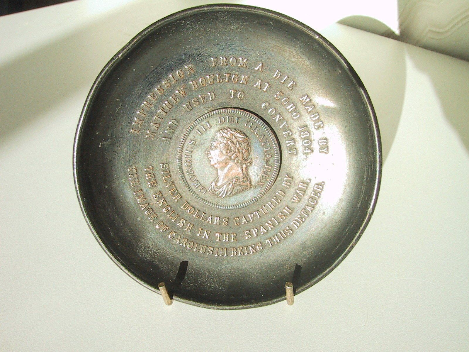 FAUX IMPRESSION FROM A DIE MADE BY MATTHEW BOULTON AT SOHO 1804 AND USED TO CONVERT SILVER DOLLARS CAPTURED BY THE ENGLISH IN THE SPANISH WAR THE IMAGE OF CAROLUS III BEING THUS DEFACED