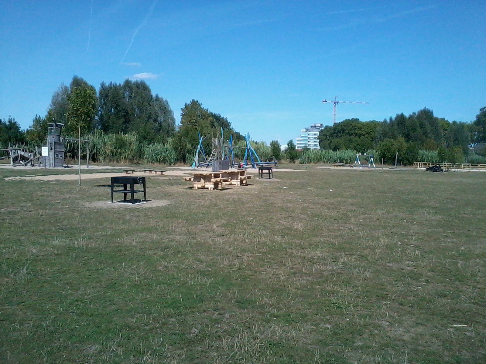 Deux tables bancs entre les barbecues, à côté des jeux d'enfants