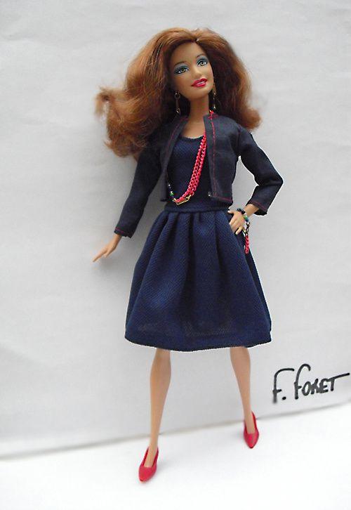 Amalia porte une robe bleu marine, petite veste assortie, escarpins rouges, bijoux