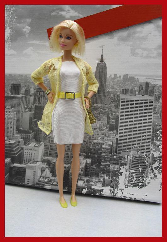 Océane porte une robe blanche, une veste longue jaune, ballerines jaune, et ceinture assortie, sac doré