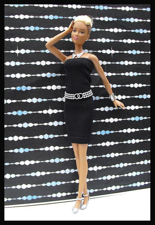 Lola porte une robe noire, ceinture argent, sandales argent et sac assorti, bijoux