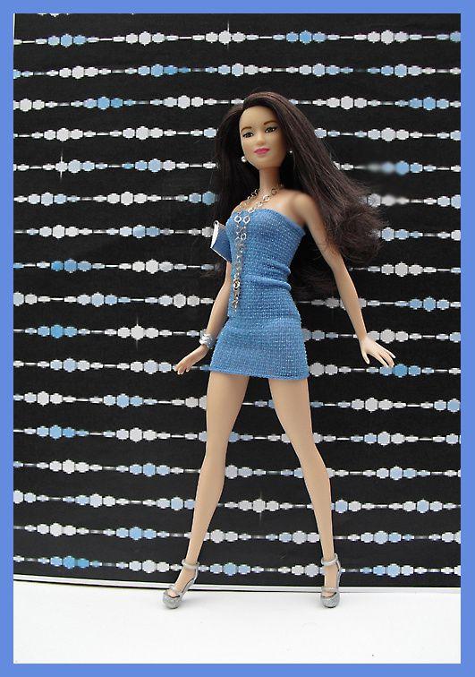Cynthia porte une mini robe bleue lamée, sandales argent, pochette argent, bijoux