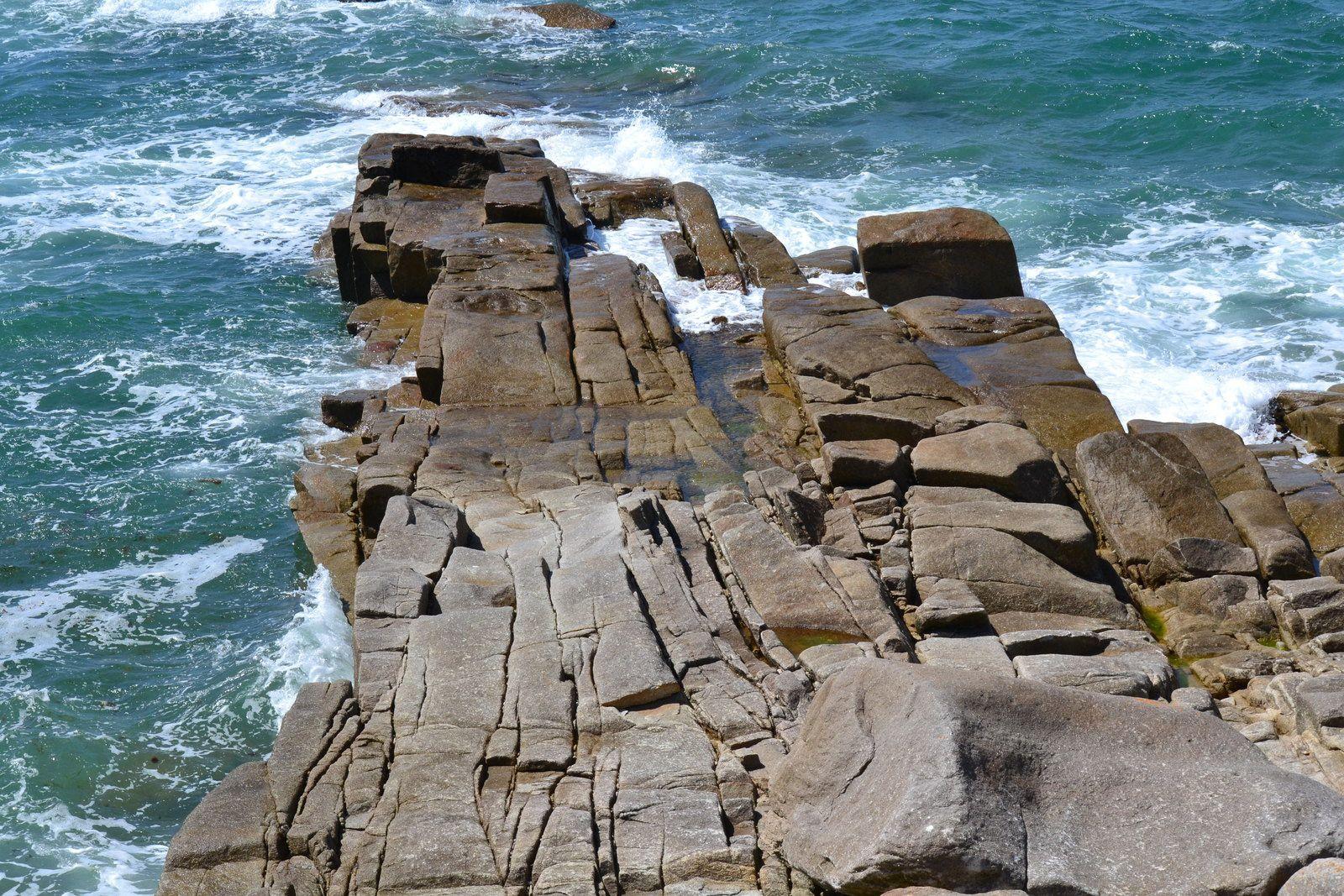 """L'exploitation du granit à l'Ile Grande  Qu'est ce que le granit ?  Le granit est un assemblage de cristaux de quartz, de feldspath et de paillettes de mica. Cet assemblage de grains, du latin """"granum"""" donna le nom de granit. A noter les deux orthographes du mot pour deux contextes différents : -granit pour les carriers et architectes -granite pour les géologues  Les origines du granit  Le granit est une roche éruptive surgie des profondeurs magmatiques de la terre. Des fissures se produisant dans la croûte terrestre, sous forte pression du magma, ce dernier atteint la surface du globe donnant les volcans. Or, ce n'est que lorsque le magma arrête sa montée vers la surface qu'il constitue le granite, sorte de volcan """"avorté"""". Le granit s'est donc formé dans le Trégor il y a 300 millions d'années lorsqu'une poche énorme de magma s'est formée sous terre à 4 ou 5 km de profondeur, allant de Trébeurden à Ploumanac'h. Quelques centaines de milliers d'années plus tard, le magma fut complètement refroidi. Ce long refroidissement a favorisé la formation de cristaux de minéraux. Plus le refroidissement est long, plus ces grains de minéraux sont gros. Voilà donc notre granite qui fut rendu visible grâce à l'érosion progressive des sols, découvrant ainsi les roches cachées dans la profondeur de la terre."""