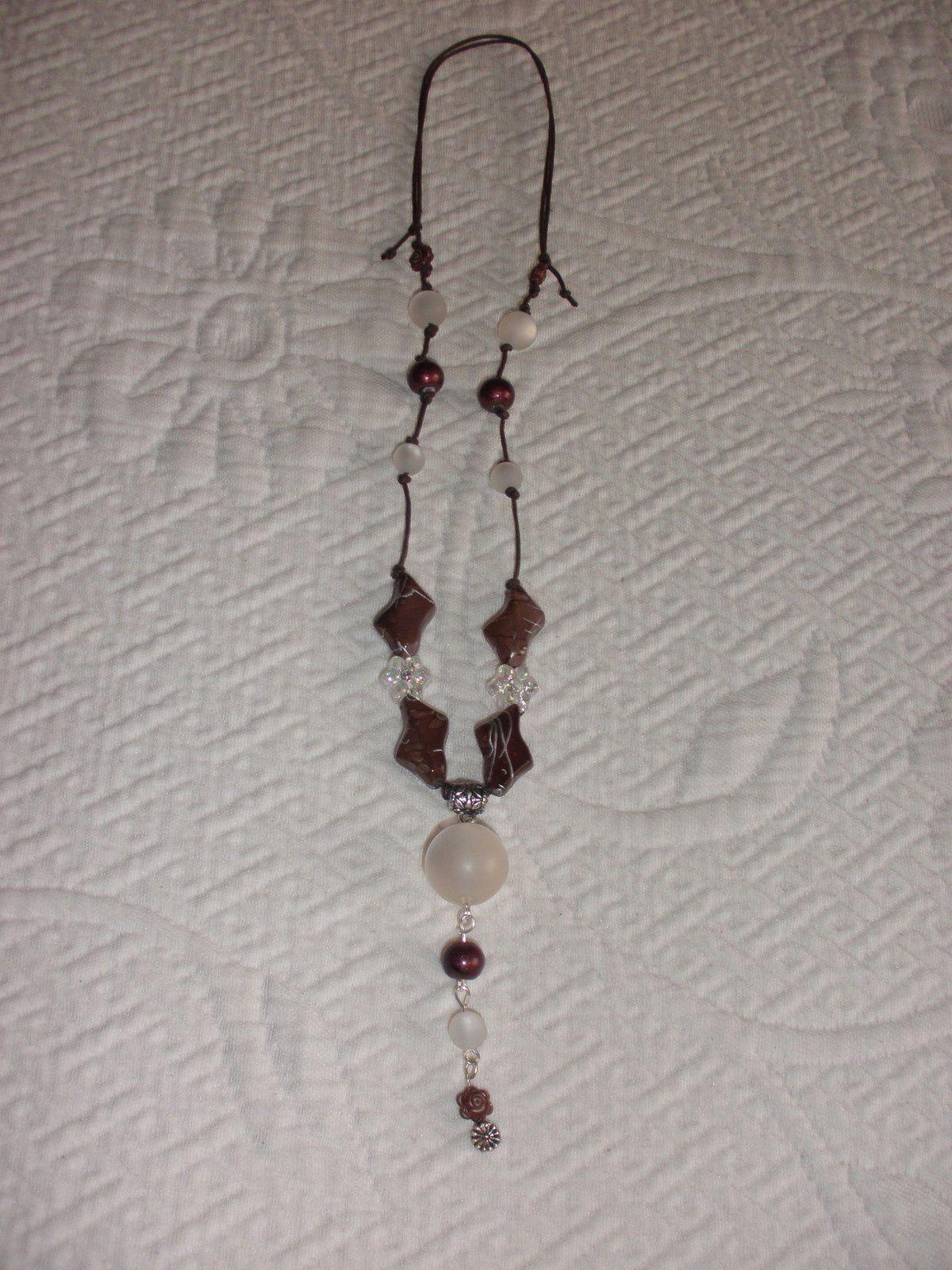 Des perles en forme de fleurs  agrémentent ce collier dont on voit la transparence.