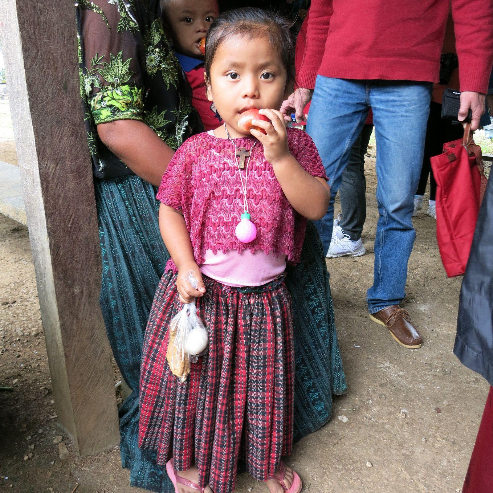 Dans la région de l'Alta Verapaz, la fillette porte le costume traditionnel, jupe froncée et blouse ajourée. Dans les Hautes Terres, la jupe de même tissu, est un simple morceau d'étoffe maintenu à la taille par une large ceinture.