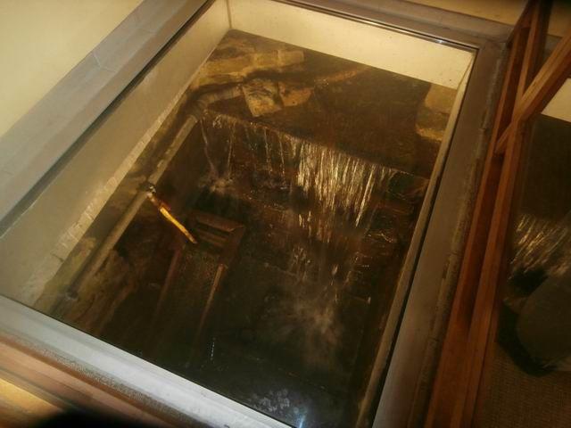 Mais rapidement un groupe se forme au-dessus de cet endroit où l'on voit l'eau qui s'écoule sous le bâtiment...