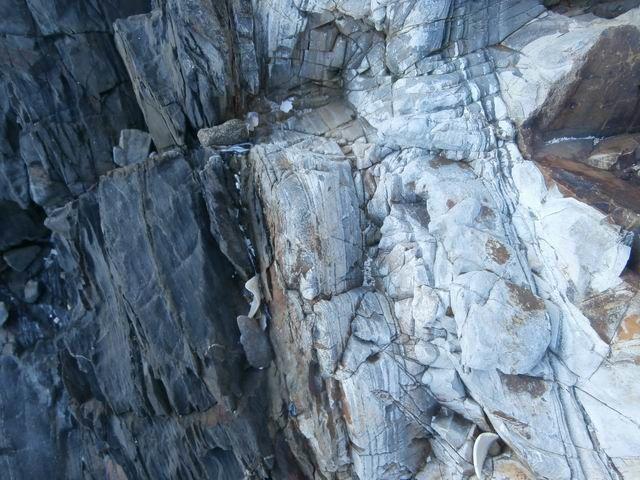 On y voit des roches litées : certaines de couleur claire (des quartzites)... mais la plupart (comme à gauche) de couleur sombre.