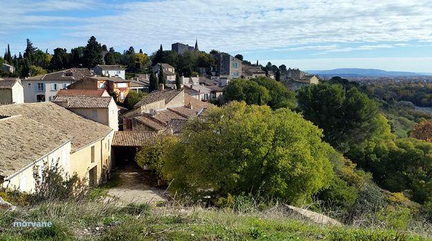 Du plateau, le village perché s'offre au regard. La montagne bleue que l'on aperçoit au fond est le Lubéron.