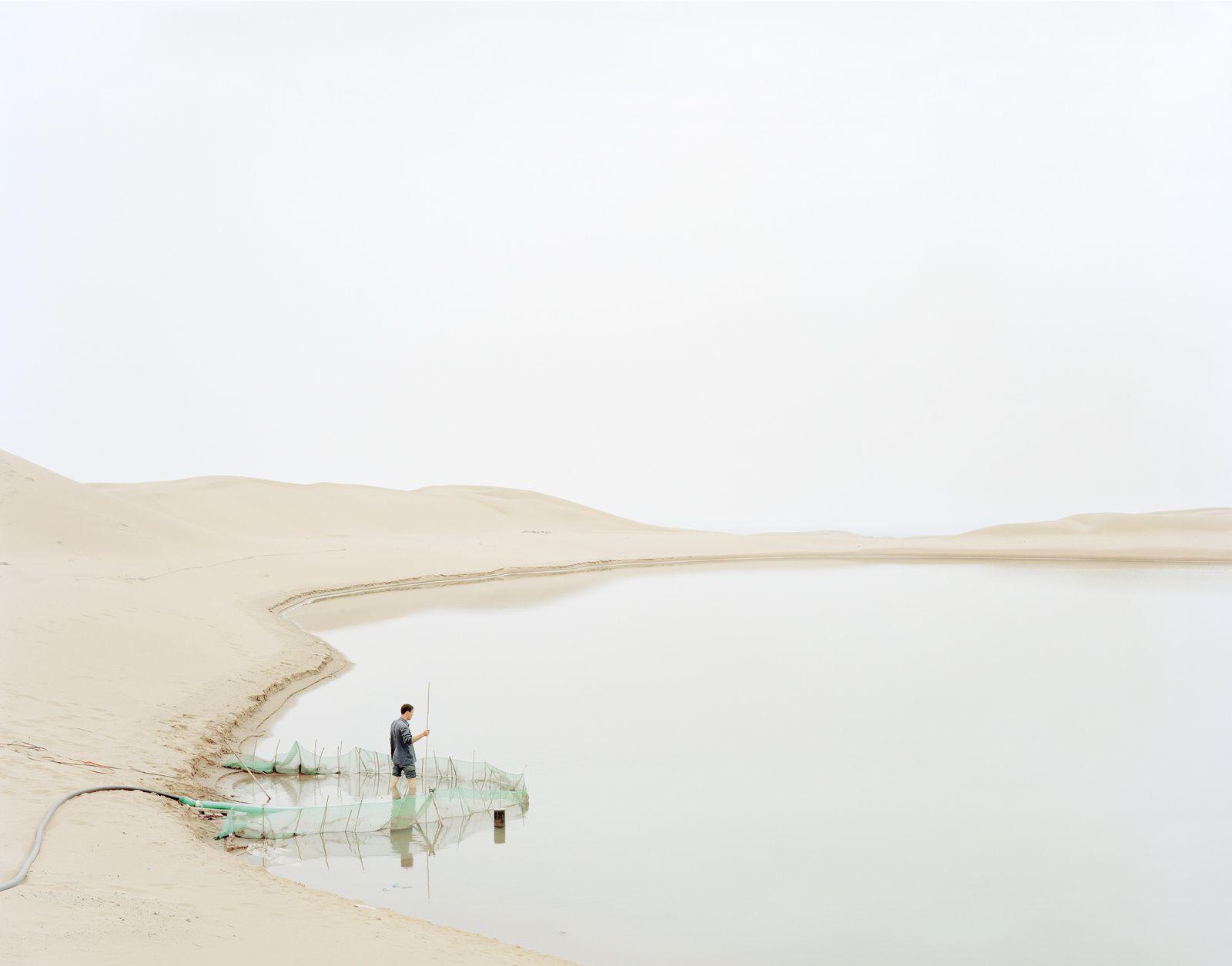 Kechun Zhang, Homme puisant de l'eau dans le terrain vague, province du Ningxia, 2011.Copyright Rencontres Arles