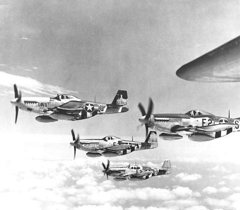 Trois P-51D et un P-51B du 361st FG en vol, au-dessus de l'Angleterre le 26 juillet 1944. Les appareils emportent deux réservoirs auxiliaires de 284 l. (origine Wikipedia)