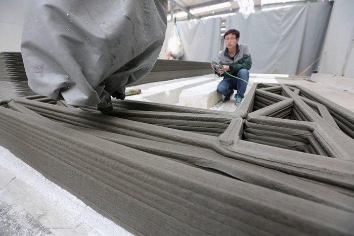 'imprimante 3D développée par le groupe chinois est imposante, elle mesure 32 mètres de long, 10 mètres de large pour 6,6 mètres de hauteur et permet de réaliser des murs en seulement quelques heures