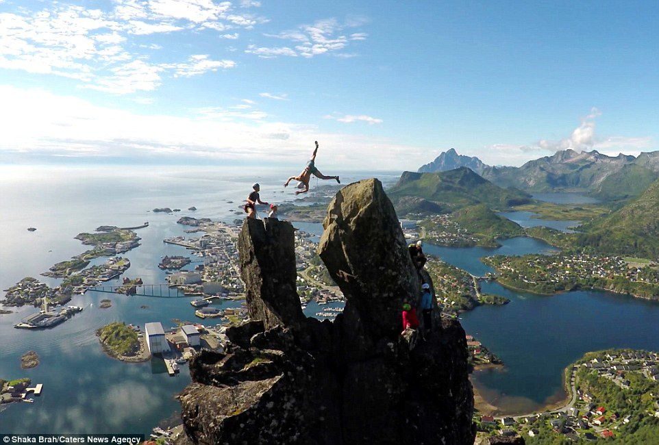 Risky business: Teenager Brage Hernes Gsvr flipped in the air between two rocks above the picturesque town of Svolvr in  Norway