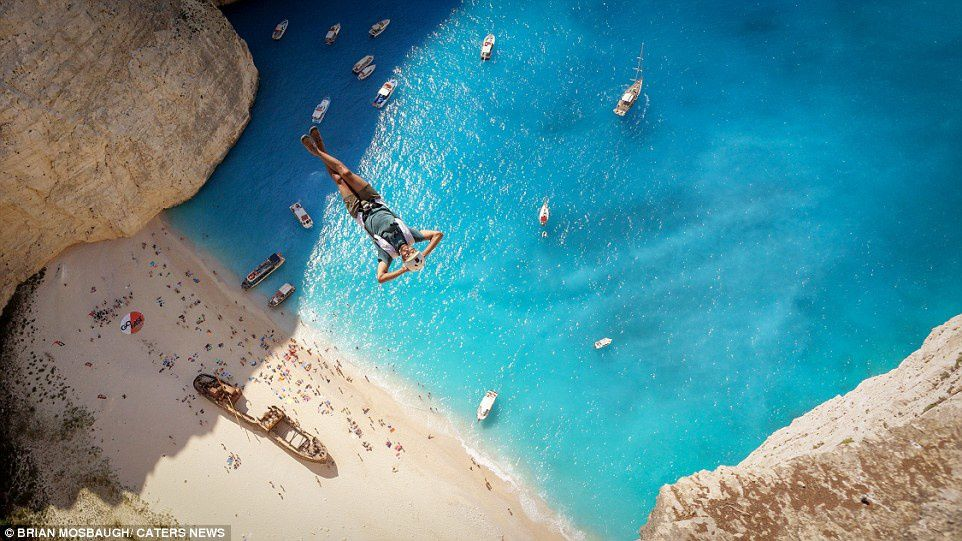 Mind-boggling: Matt Blank is pictured looking very much at ease as he performs a 650ft BASE jump over Navagio Beach, in Zakynthos, Greece