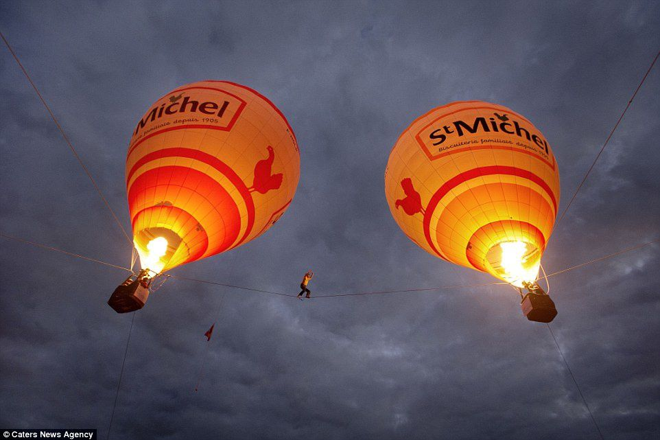 In memory: Tancrede Melet is pictured walking between two hot air balloon in southern France. The slackliner, jumper and wingsuiter from France, accidentally fell more than 100ft to his death while getting ready to perform with a hot air balloon in January
