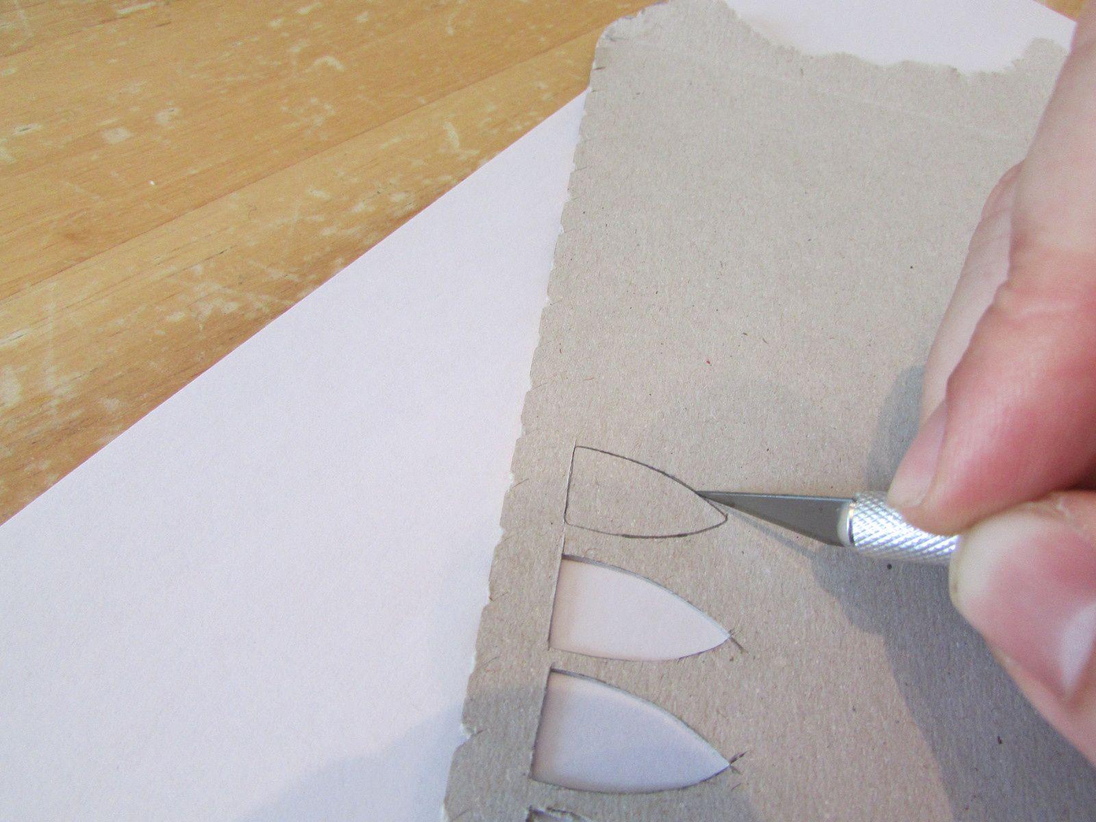 découpe du bouclier dans l'emballage céréale... pour donner la forme arrondie au bouclier, il suffit de le poser sur le cuillère en bois