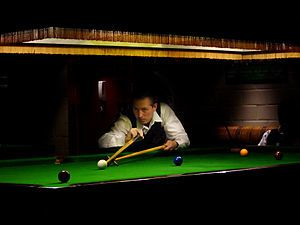 A man playing snooker on a baize-covered table...
