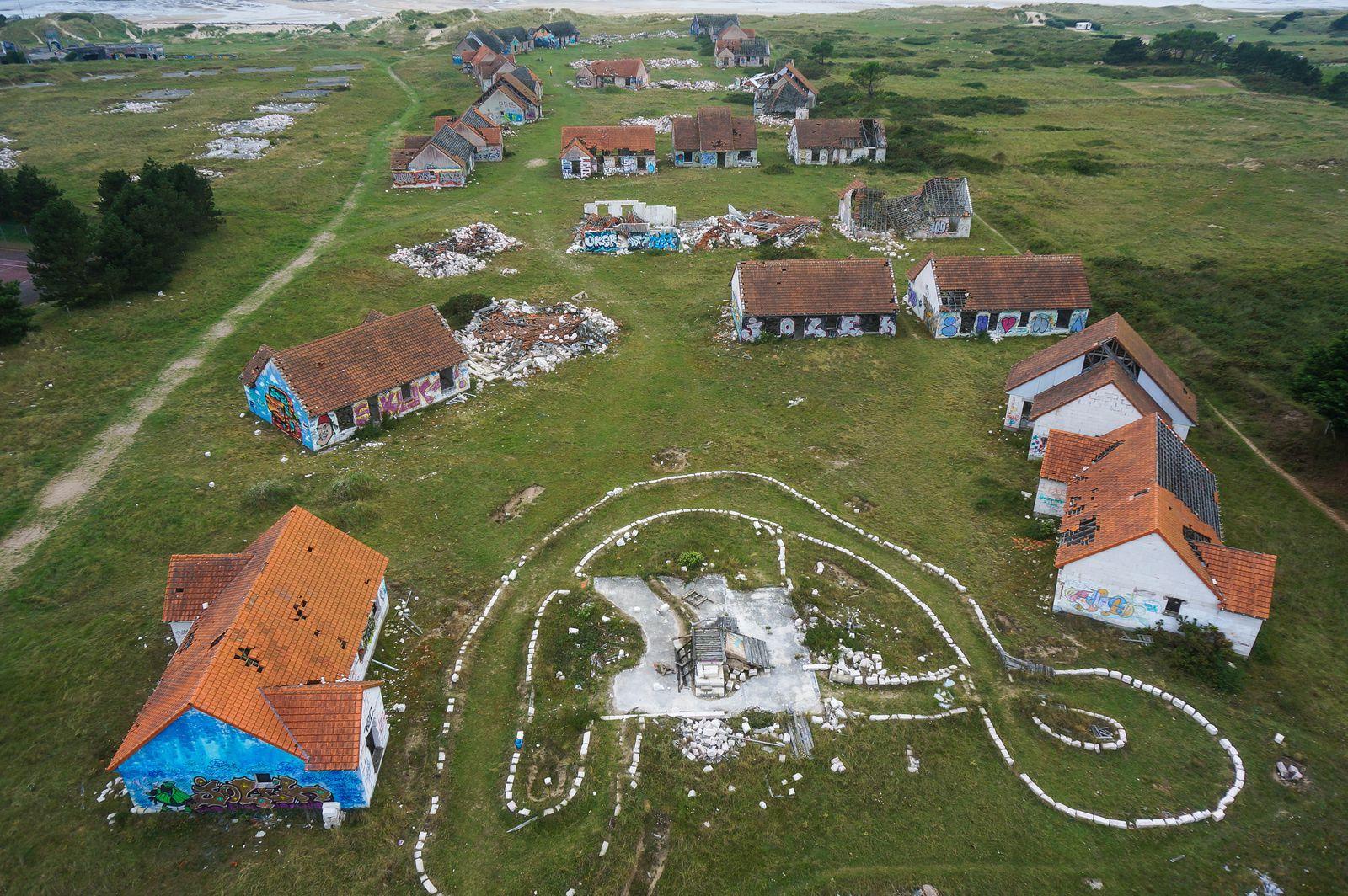 Des dizaines de maisons en ruine face à la mer, c'est tout ce qu'il reste du chantier inachevé de Pirou-plage dans les années 90. photos aériennes François Monier. Août 2015
