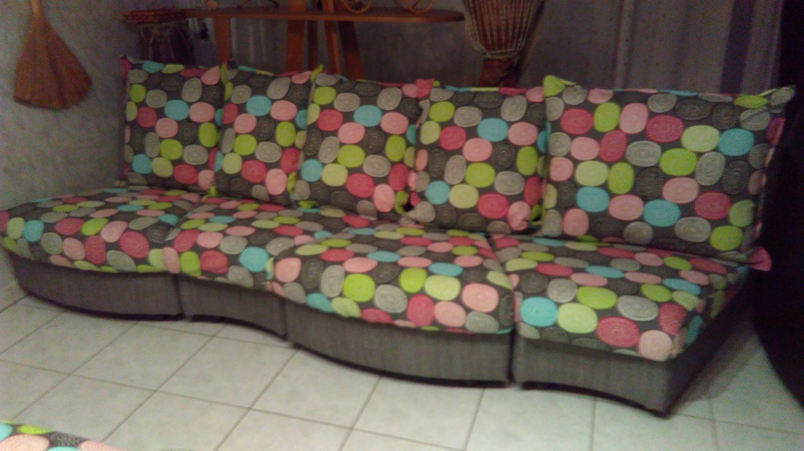 Nouveau canapé en structure grise et assies et coussins en couleur.