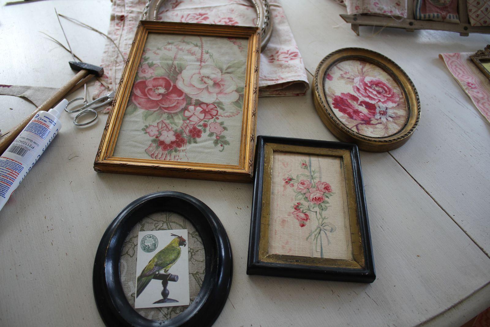 Le choix des cadres et des tissus à côté d'une réalisation d'Isabelle, préparation d'un encadrement, les tissus encadrés et un porte photos ancien.