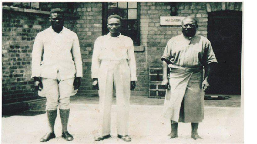 Nous avions montré cette photo à papa Honoré Nkunku. Elle fut prise en prison. Selon lui, le boy du gouverneur belge l'avait remise à papa Alexandre Nkinu qui la ramena ensuite à Kinshasa. Kimbangu porte l'uniforme des prisonniers. Comme sa vue a fortement baissé (même avec l'usage des lunettes), papa Honoré Nkunku n'avait pu distinguer et reconnaître les deux hommes à côté du prophète.