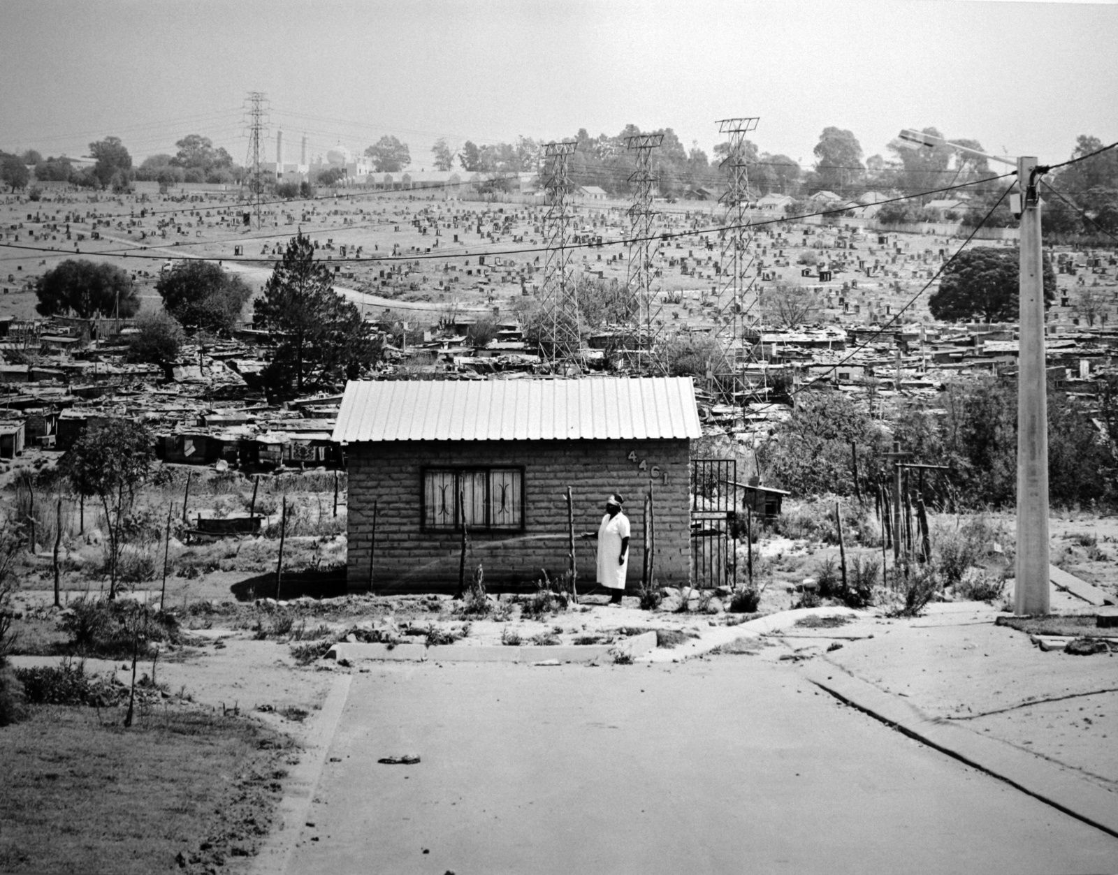 """Miriam Mazibuko waters the garden of her RDP house for which she waited eight years. Extension 8, FarEast Alexandra Township"", 12/09/2006 David Goldblatt. Courtesy of the artist and Marian Goodman Gallery, Paris"