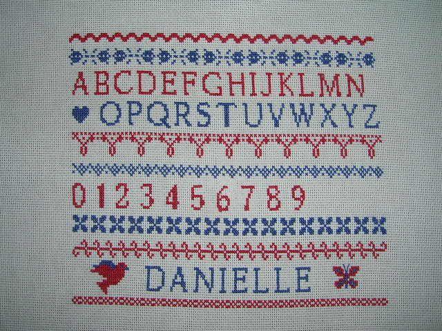 10 ème étape de la part de DANIELLE, avec l' étape 11 elle a brodé des petits motifs de chaque côté de son prénom pour personnaliser son marquoir.