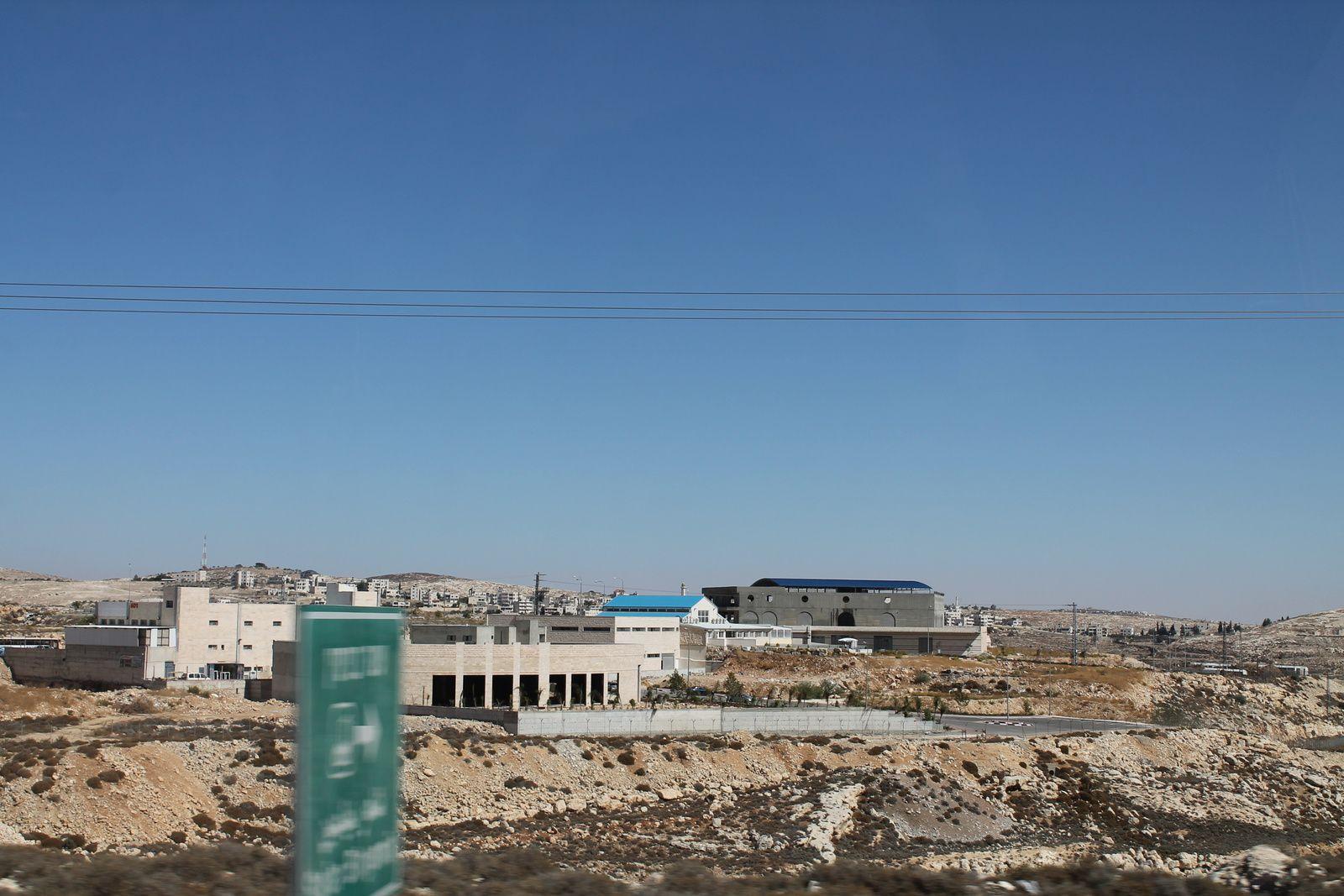 """Ce bâtiment placé entre la route palestinienne et la route des colons est appelé le """"dos à dos"""". En effet, les camions palestiniens y entrent en marche arrière et viennent se placer derrière d'autres camions à plaque israélienne orientés vers la route des colons. Les marchandises des camions palestiniens sont transvasées dans les camions immatriculés en Israël qui peuvent ainsi circuler dans le territoire de l'Etat hébreu jusqu'au port de Haïfa en cas d'exportation maritime. On se doute que ce système absurde entrave fortement l'économie palestinienne !"""